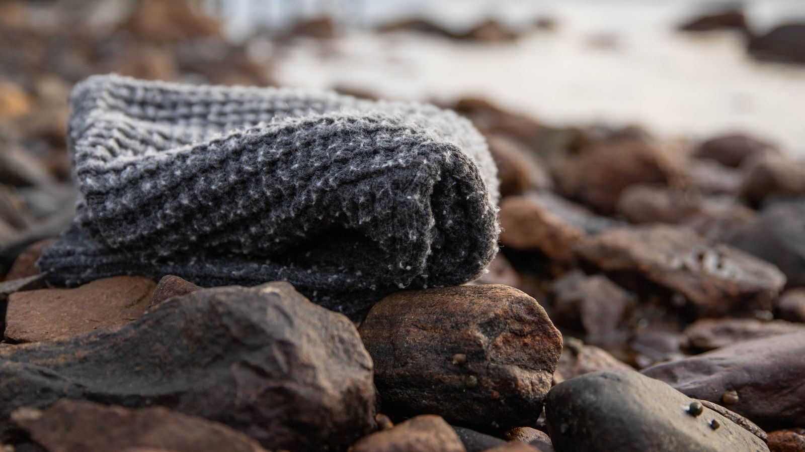En grå nuppete genser av plast på stranda