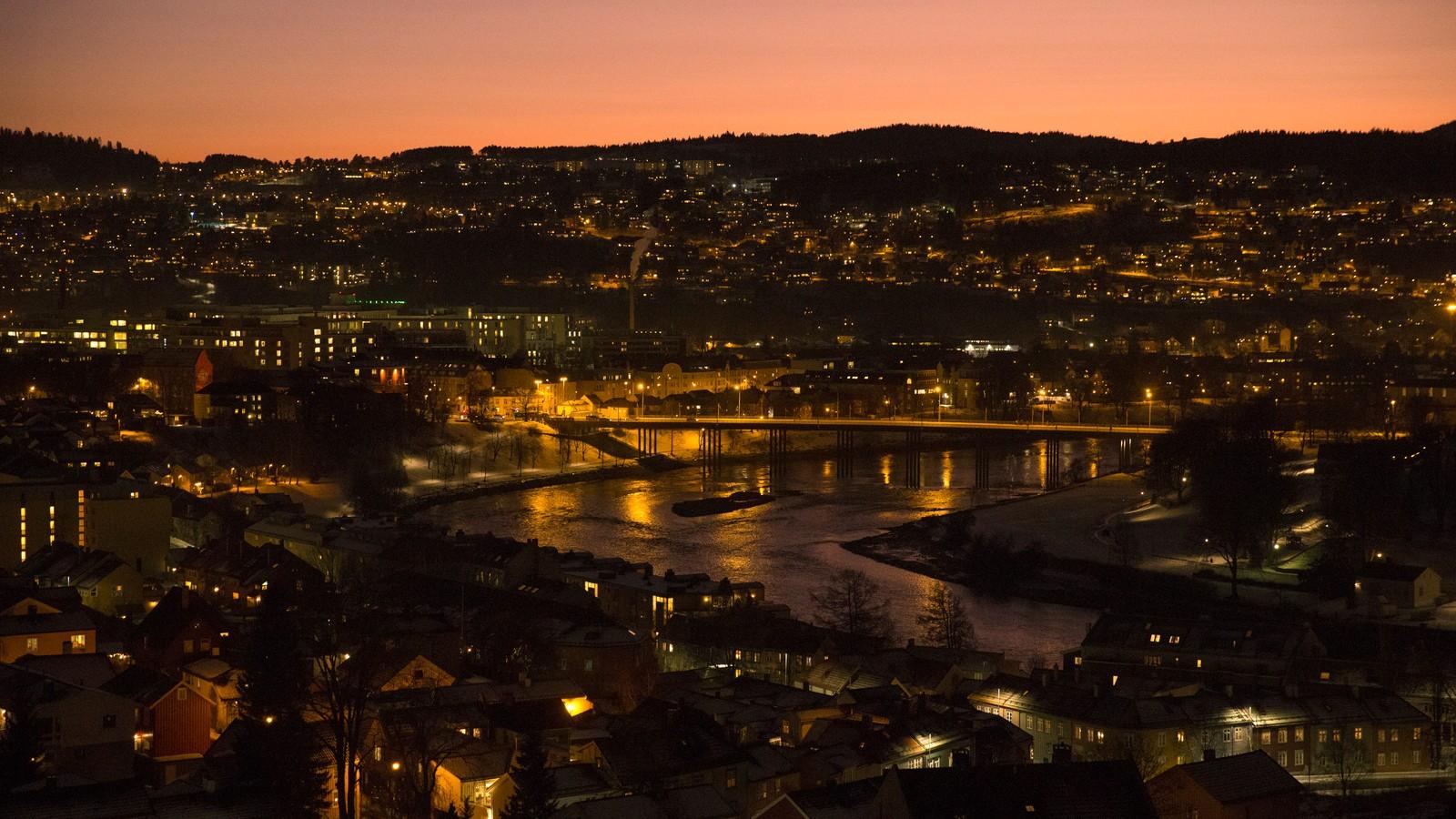 Trondheim by på kvelden med rødskjær på himmelen og lysene som glitrer.