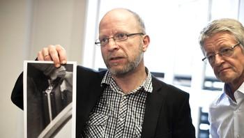 Geir Selvik Malthe-Sørenssen holder opp et bilde av Treholt-kofferten, bak ham står Harald Stabell