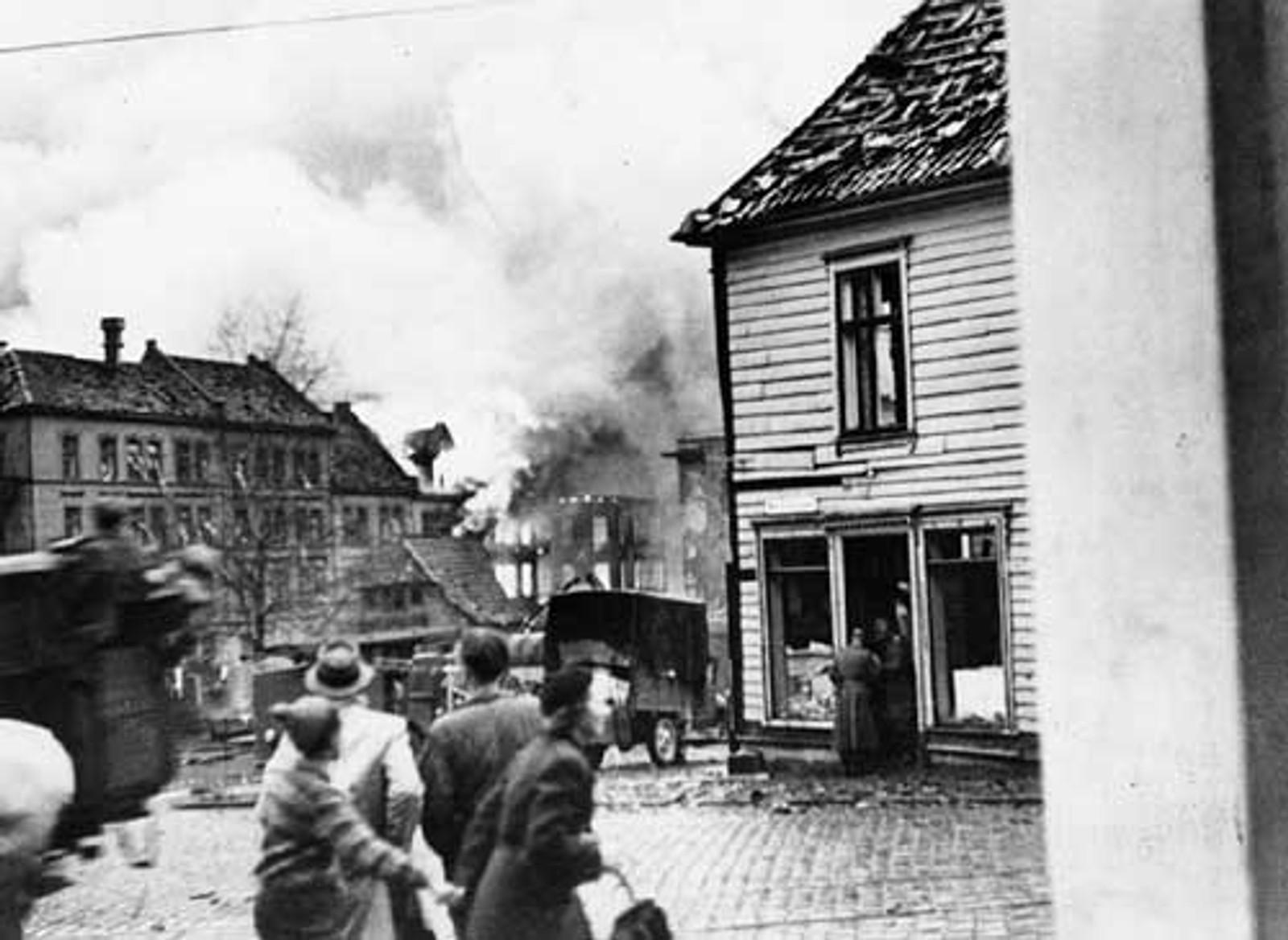 BOMBING PÅ NORDNES: Folk løper i dekning mens tyske soldater plyndrer butikkene.