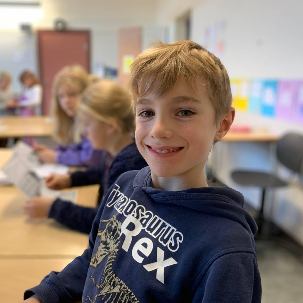 Johannes sitter ved pulten i klasserommet.
