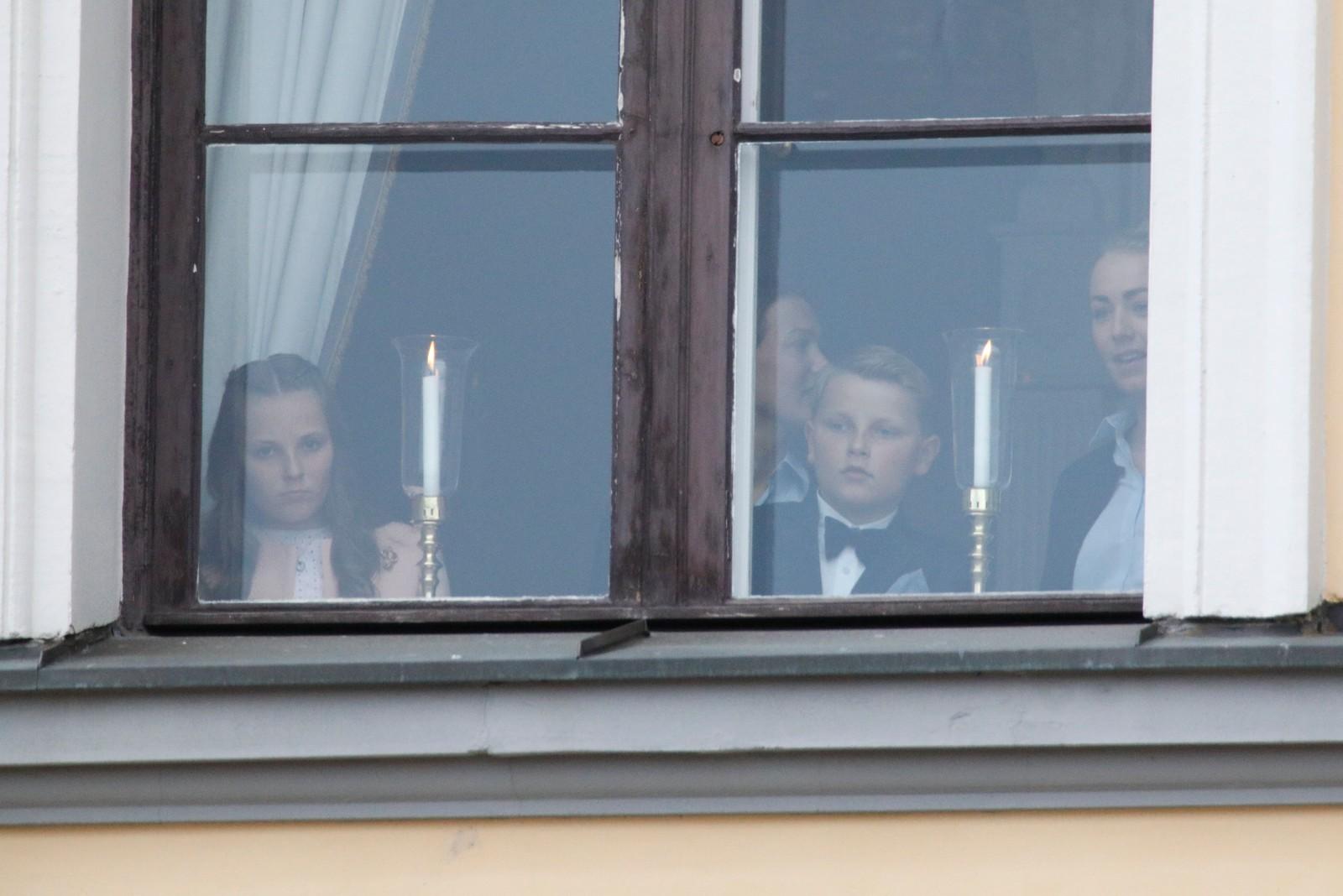 Prinsesse Ingrid Alexandra og Prins Sverre Magnus ser ut over underholdningen på slottsplassen i anledning kongeparets 80-årsfeiring.