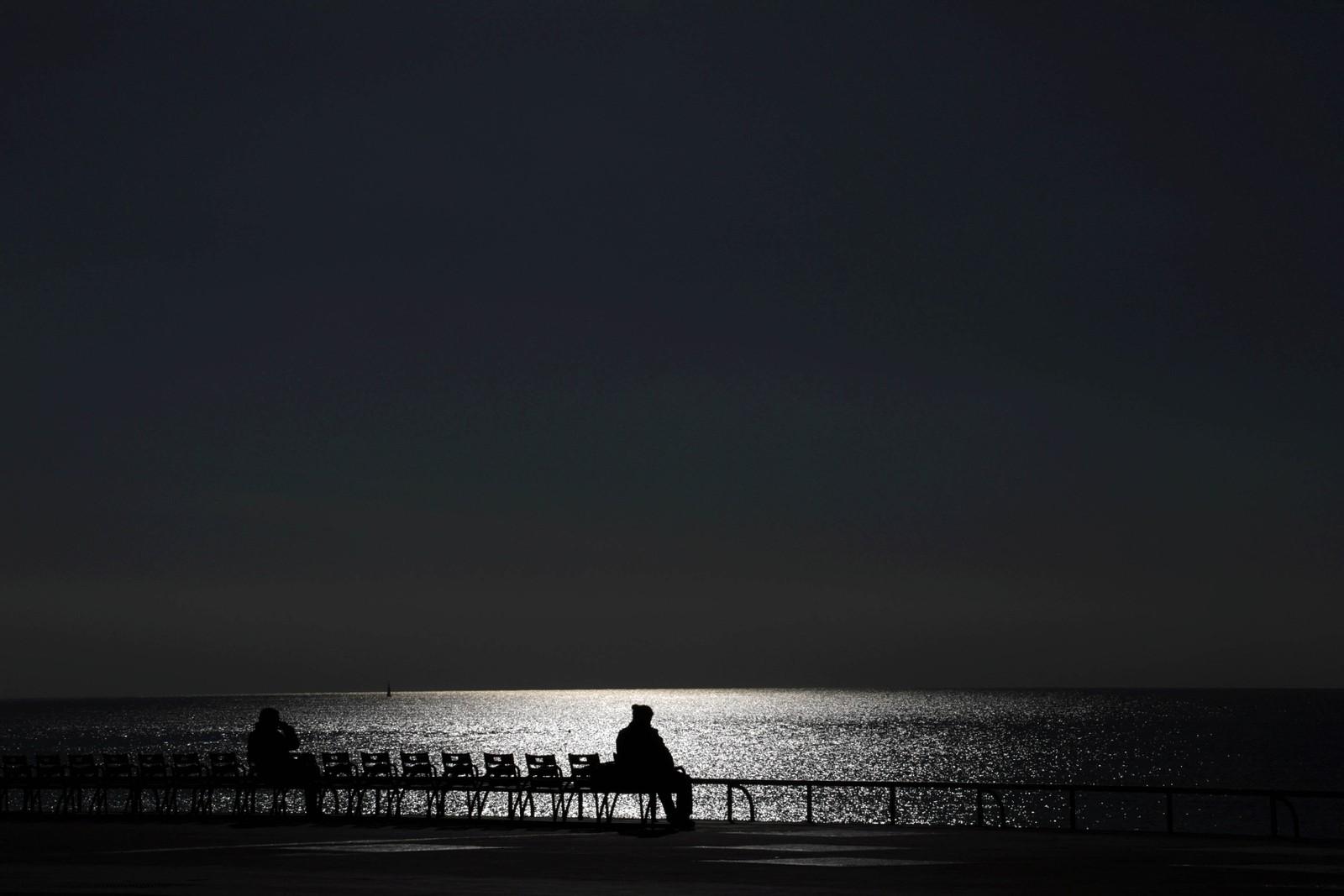 Mennesker nyter en varm og solrik dag på Promenade des Anglais i Nice i Frankrike.