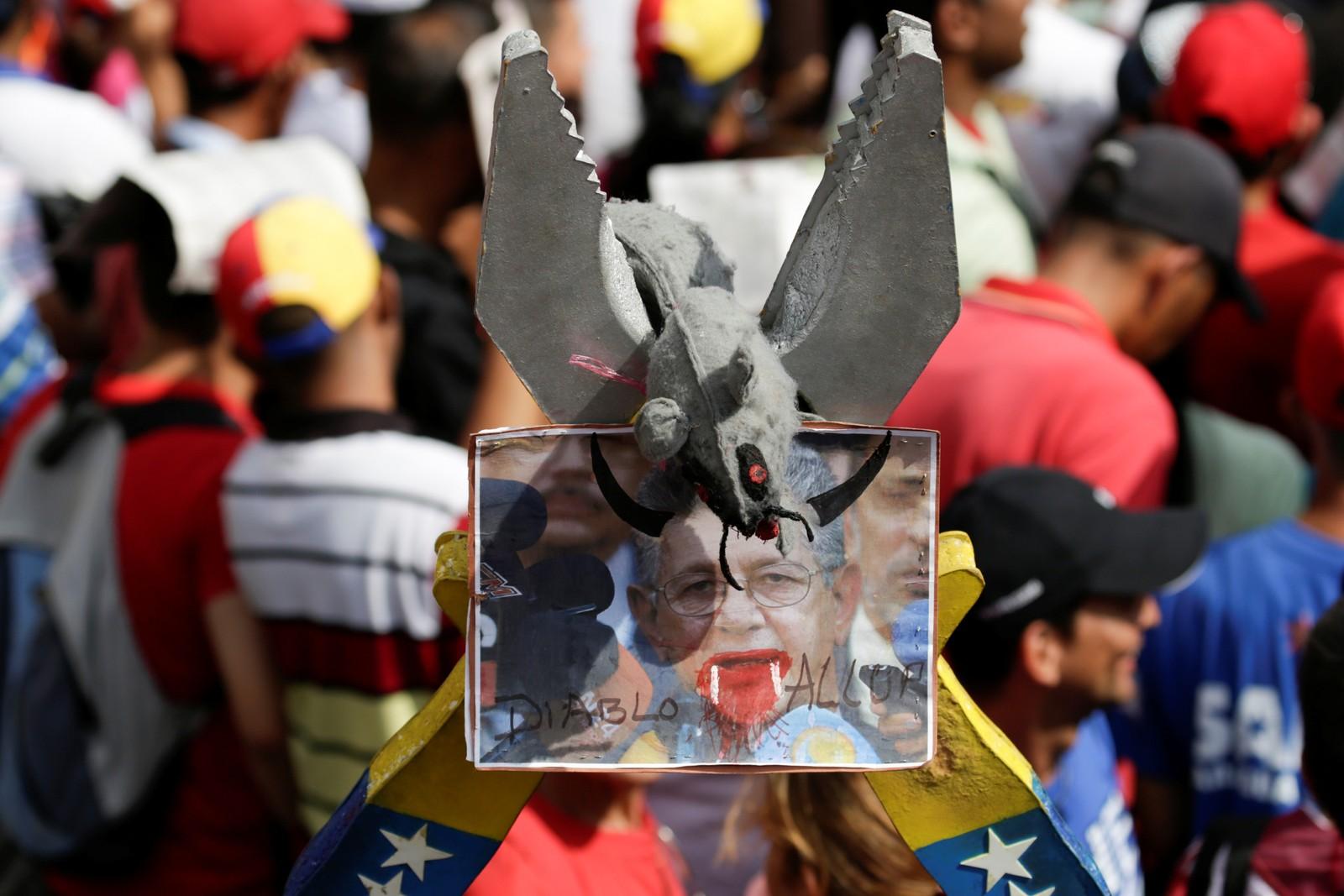 Tilhengere av president Maduro viser fram et bilde av Henry Ramos Allup, presidenten i nasjonalforsamlingen. Bildet viser Allup som en djevel.