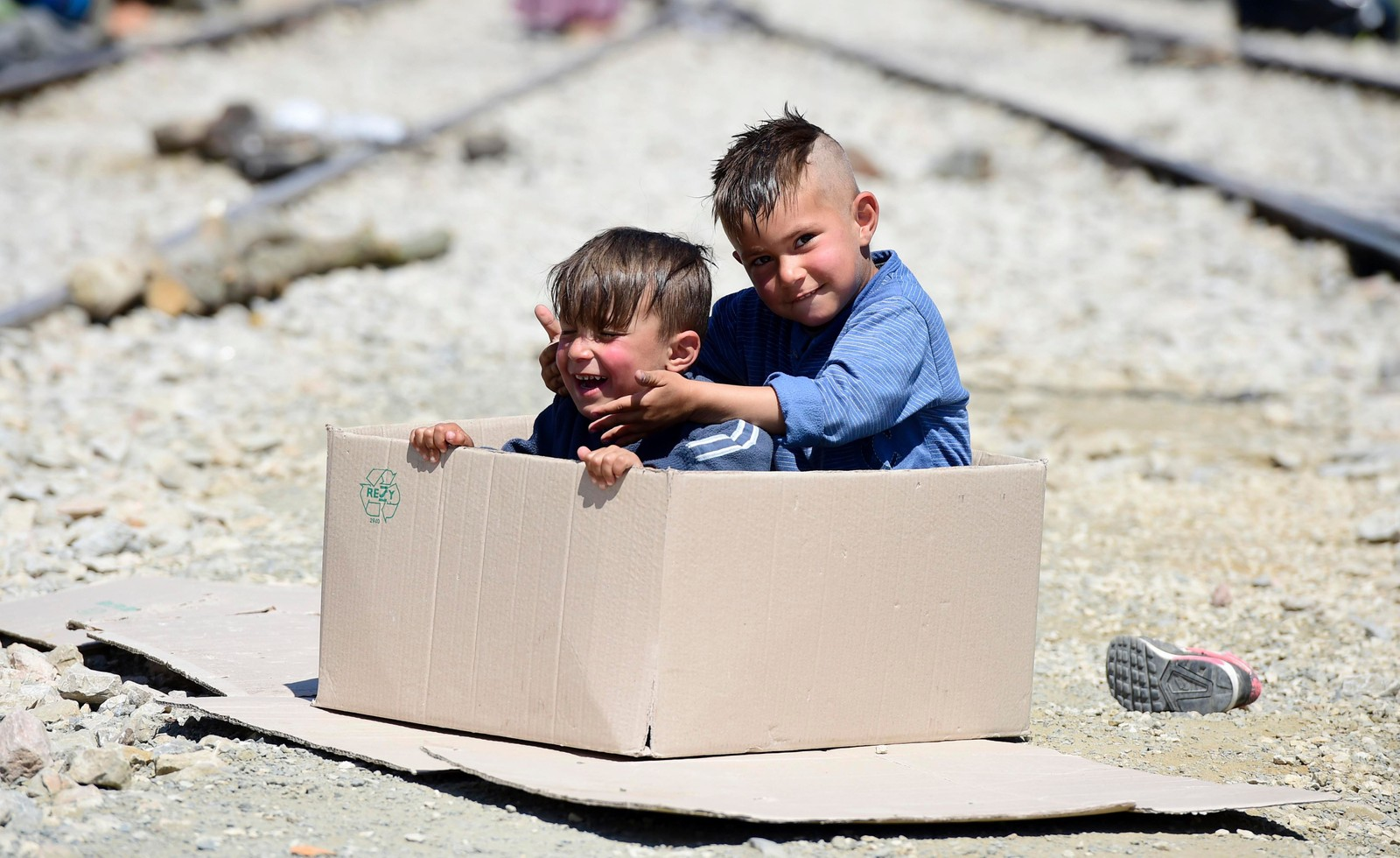 To unge gutter leker i en pappeske i den midlertidige flyktningleiren nær Idomeni på grensen mellom Hellas og Makedonia torsdag denne uken. Rundt 54.000 mennesker sitter fast i Hellas etter at grensene på Balkan ble stengt i februar.
