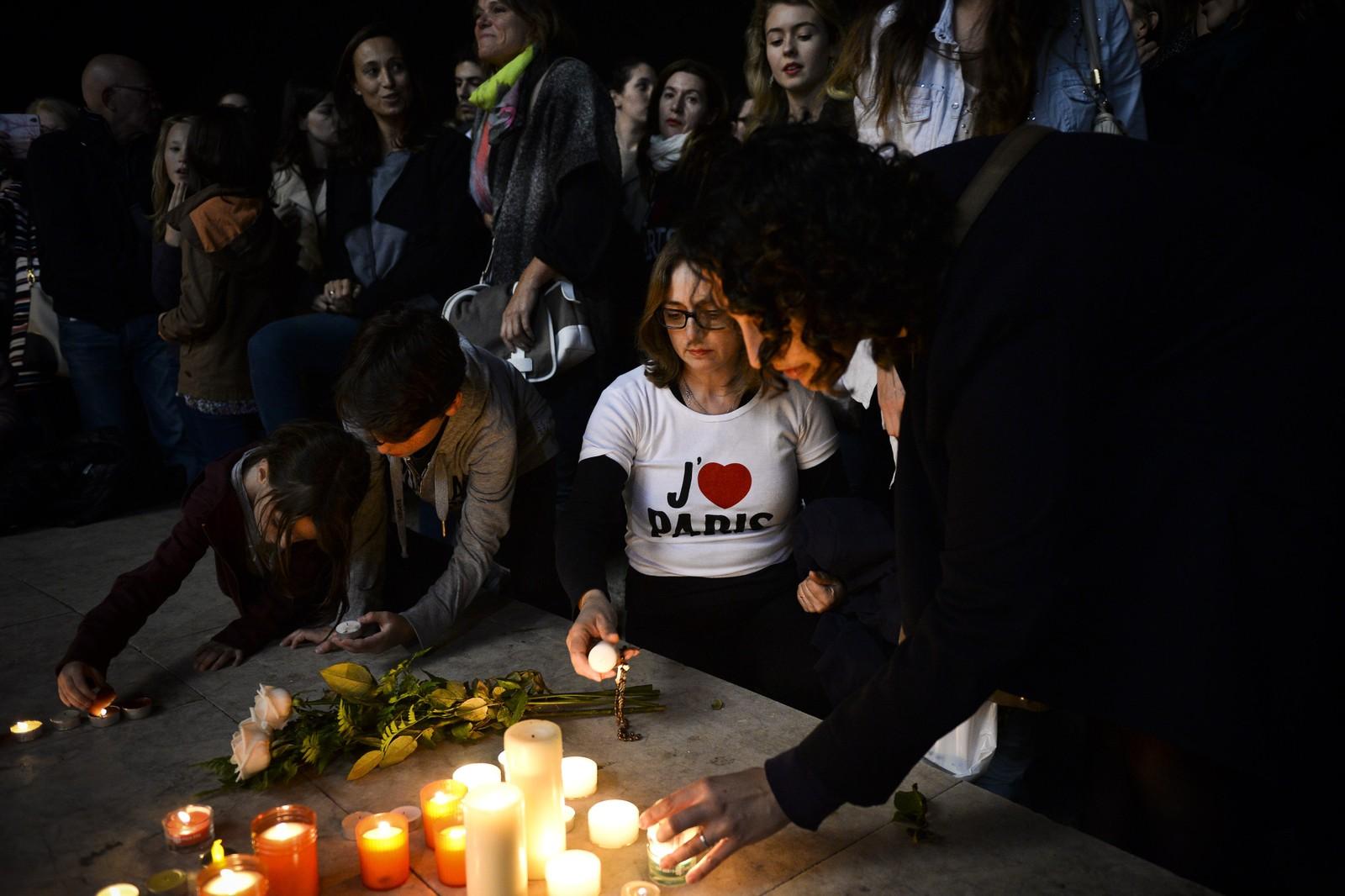 En portugisisk kvinne tenner lys for Paris-ofrene i Lisboa.