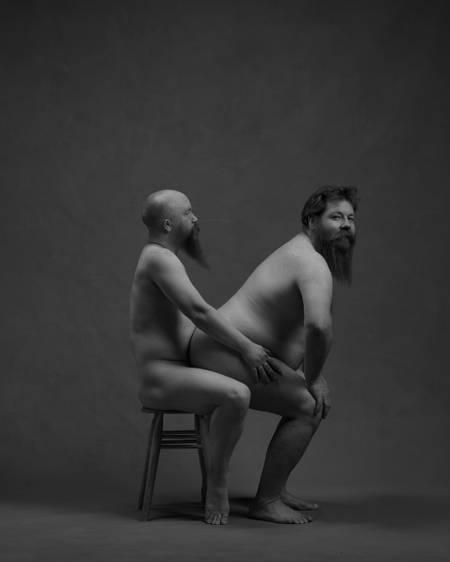 En naken mann uten hår, med langt skjegg, sitter på en trekrakk. Han holder på hoftene til en naken skjeggete mann som sitter på fanget hans