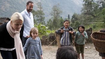 Kronprinsfamilien i samtale med barn som er på veg ut for å hente gras til kyrne