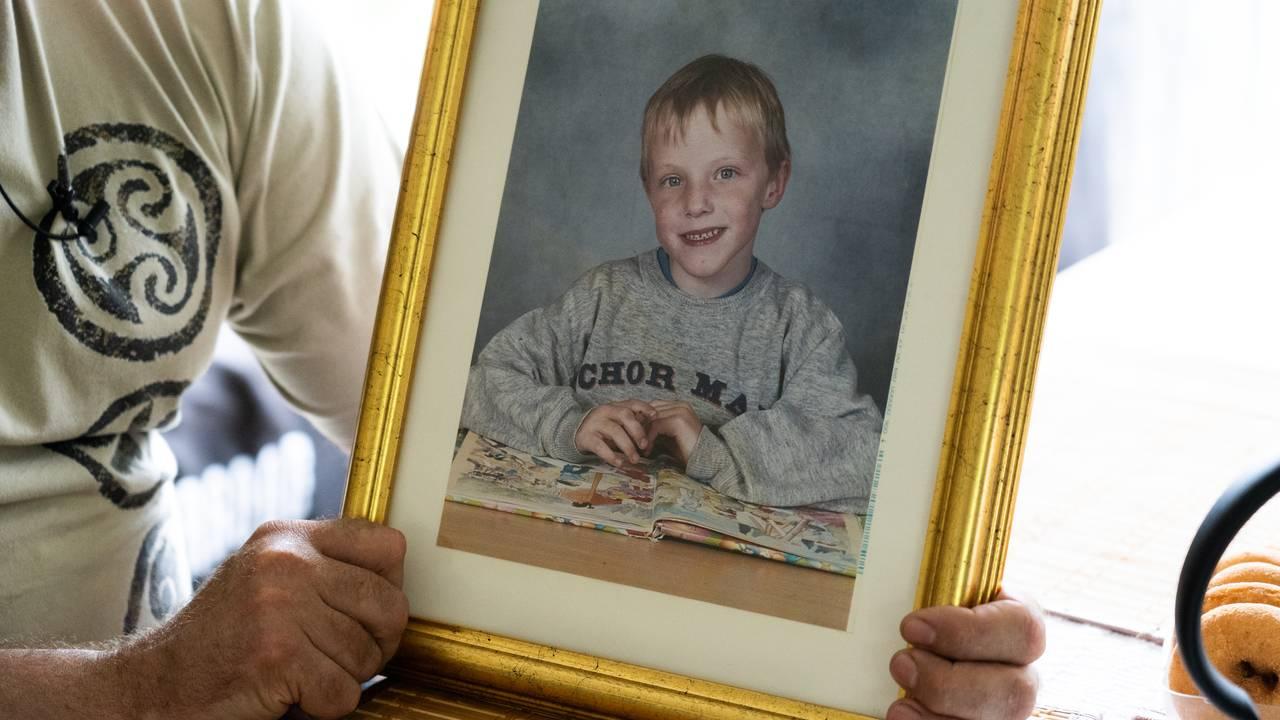 Roger Åsheim holder bildet av sønnen Johannes som ble angrepet av seks hunder og døde.