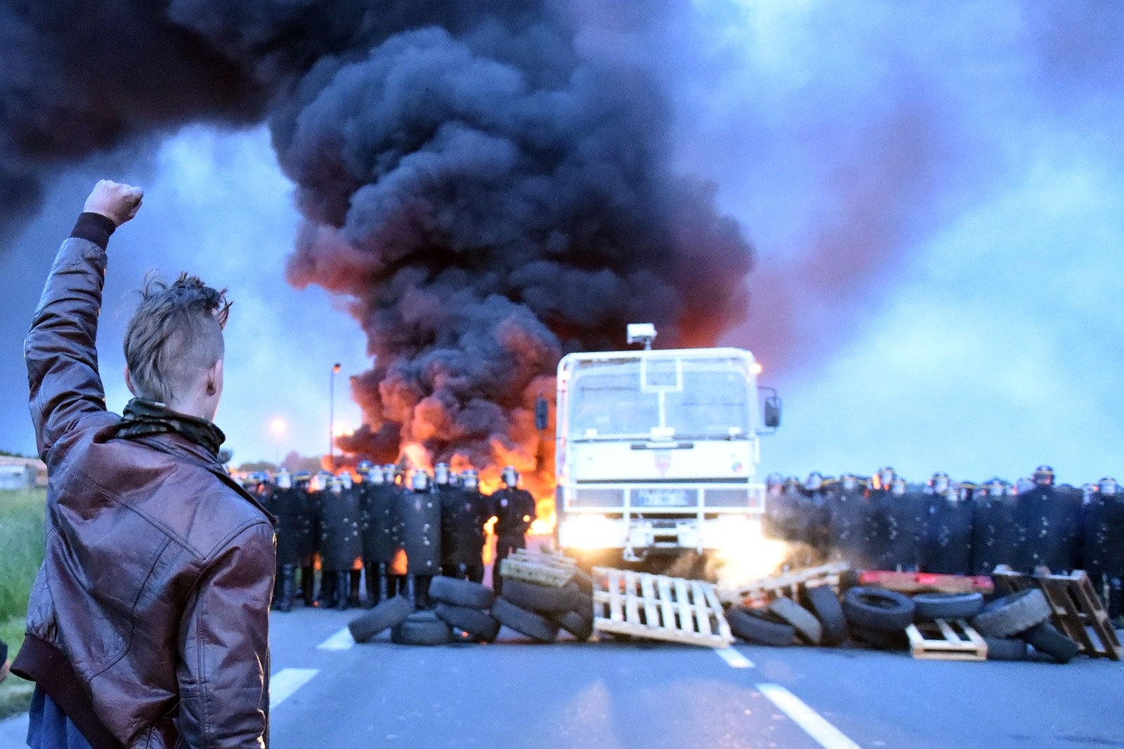 DEMONSTRASJON 3: Opprørspoliti tok oppstilling foran streikende arbeidere som blokkerte inngangen til et oljeraffineri i Douchy-Les-Mines, Frankrike. Demonstrantene protesterer mot arbeidslivsreformene den franske regjeringen vil innføre.