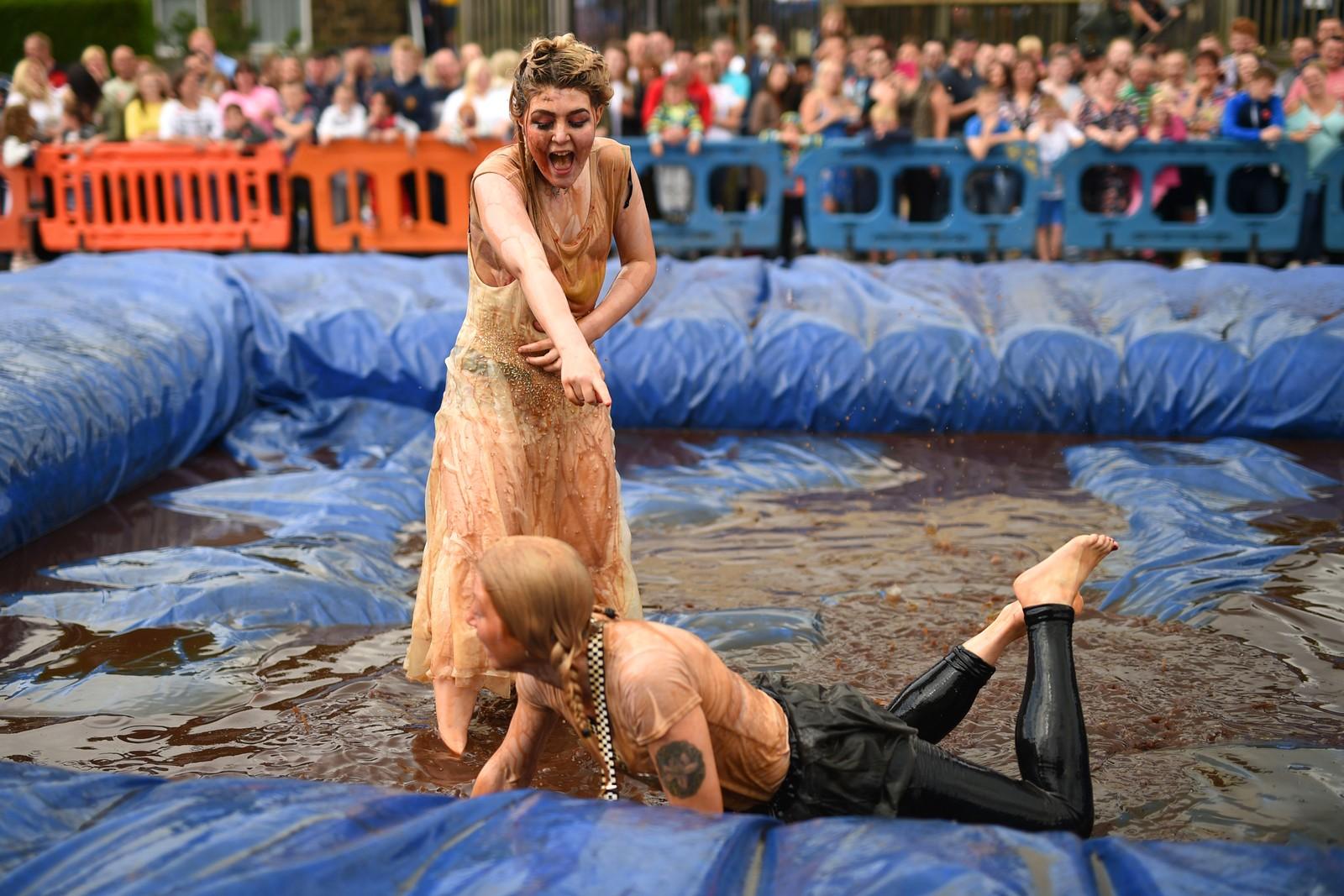 """Litt skadefryd må være lov når motstanderen har havnet i sausen. Dette bildet er fra den tiende utgaven av """"World Gravy Wrestling Championships"""" som arrangeres ved Bacup i England. Deltakerne kler seg ut og bryter i to minutter i et basseng med sjy."""