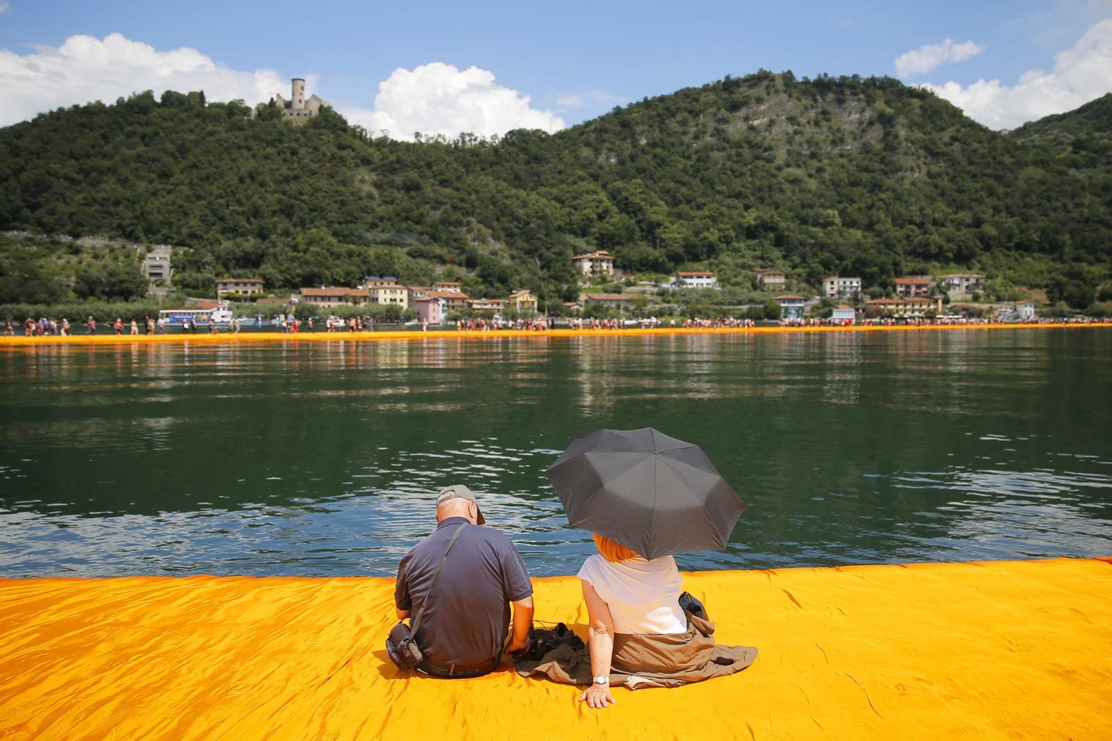 Et par nyter utsikten mot land fra «The Floating Piers». Mer enn 270.000 mennesker har besøkt installasjonen på de fem dagene siden åpningen.