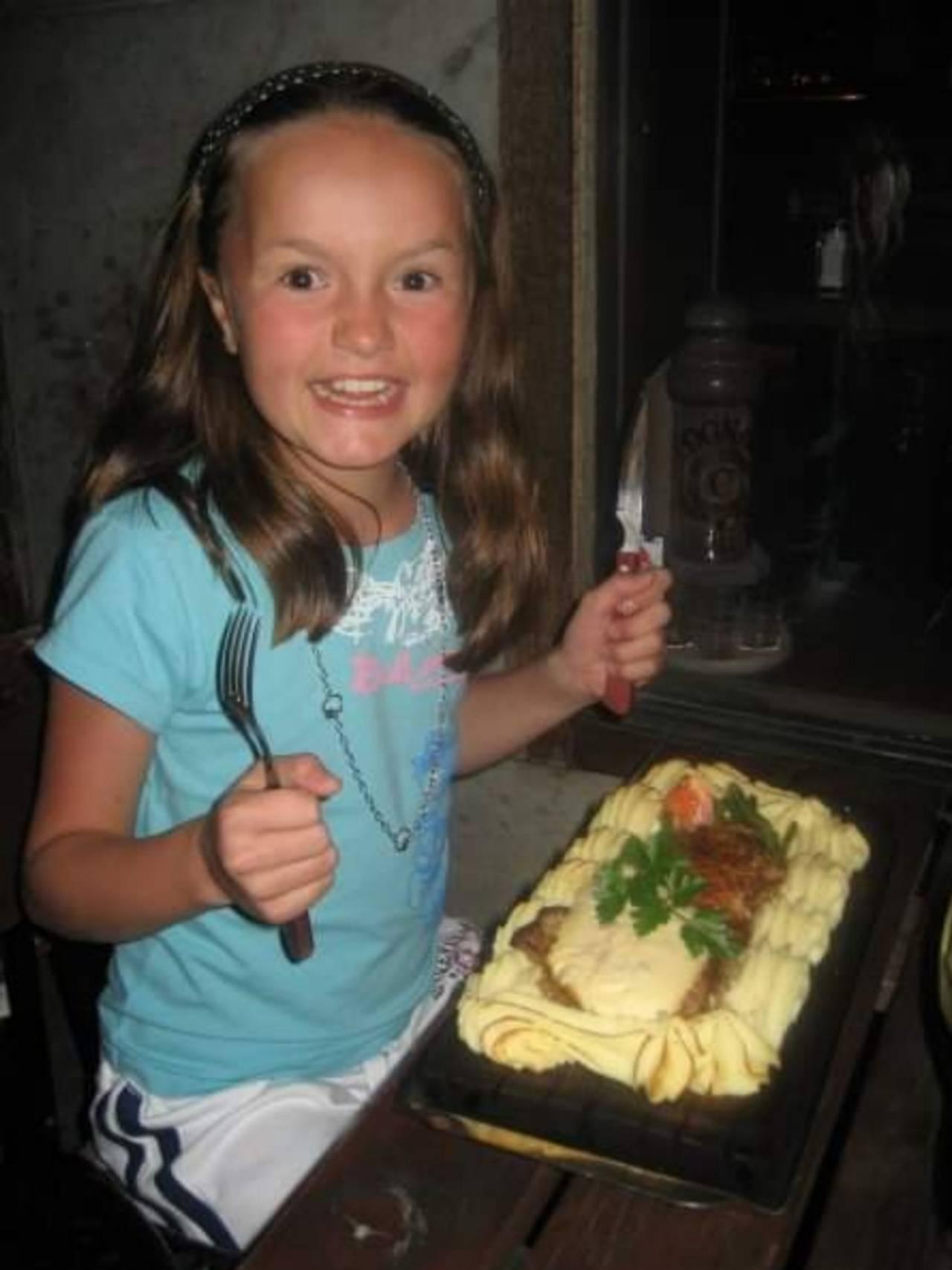 Andrine sitter på restaurant gliser til kamera og holder kniv og gaffel opp i lufta.