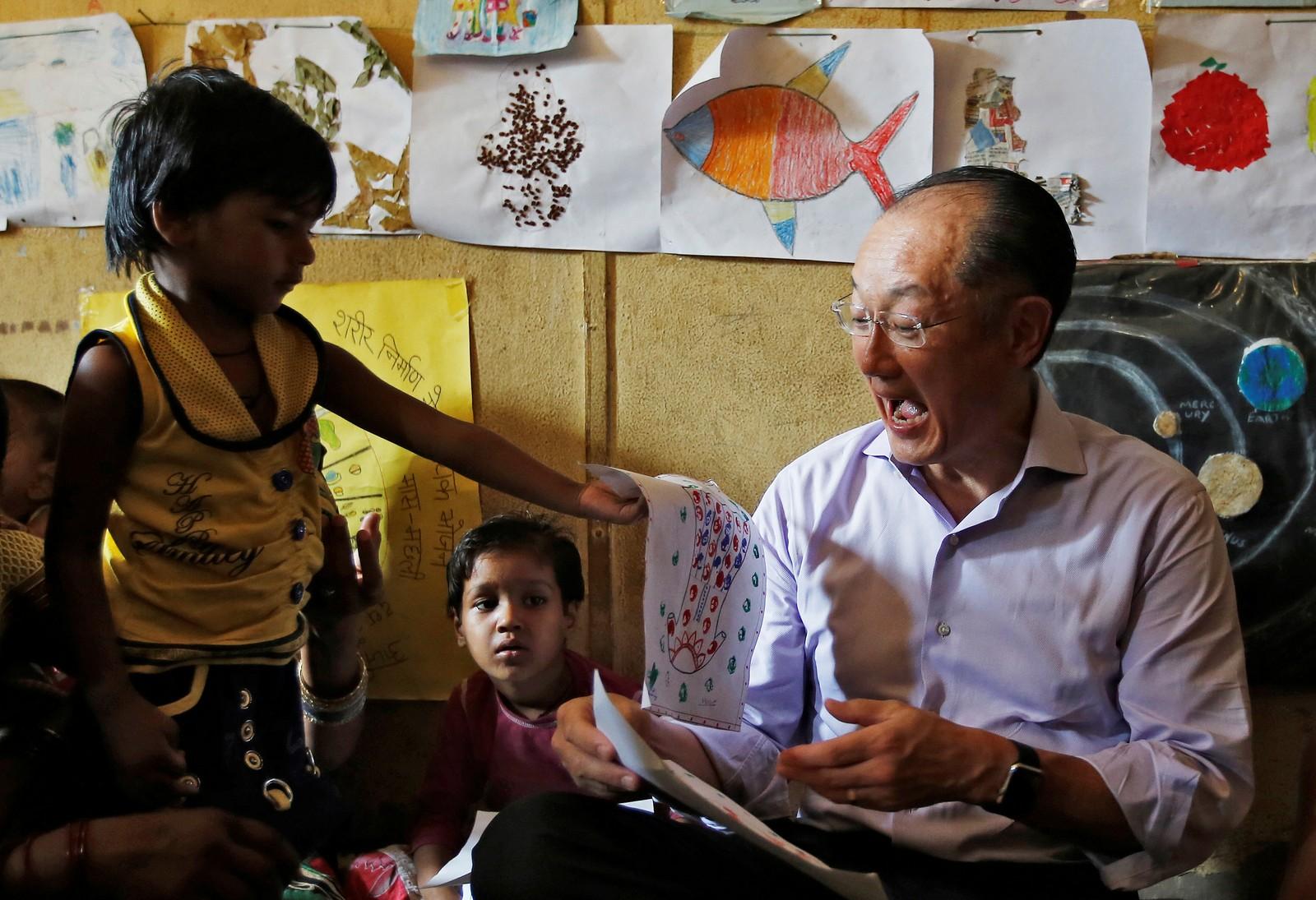 President i Verdensbanken, Jim Yong Kim, får en tegning av en liten jente under et besøk i New Dehli i India.