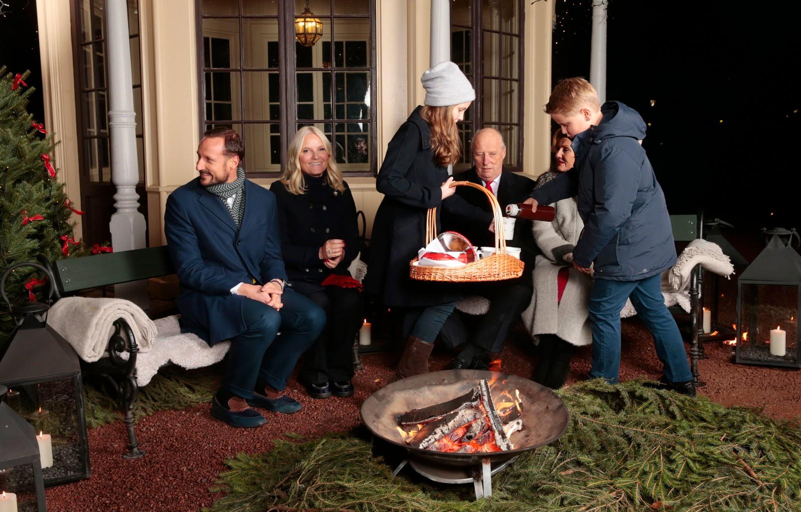 Kronprins Haakon, prins Sverre Magnus, kronprinsesse Mette-Marit, kong Harald, prinsesse Ingrid Alexandra og dronning Sonja drikker gløgg av kopper prinsesse Astrid har malt og spiser pepperkaker utenfor lysthuset på Slottet i forbindelse med julefotografering tirsdag ettermiddag.