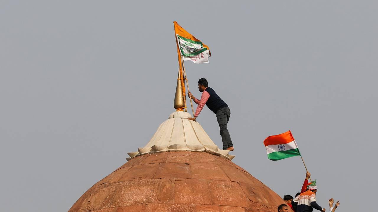 En demonstrant henger opp et flagg på toppen av Det røde fortet i Delhi, 26. januar.