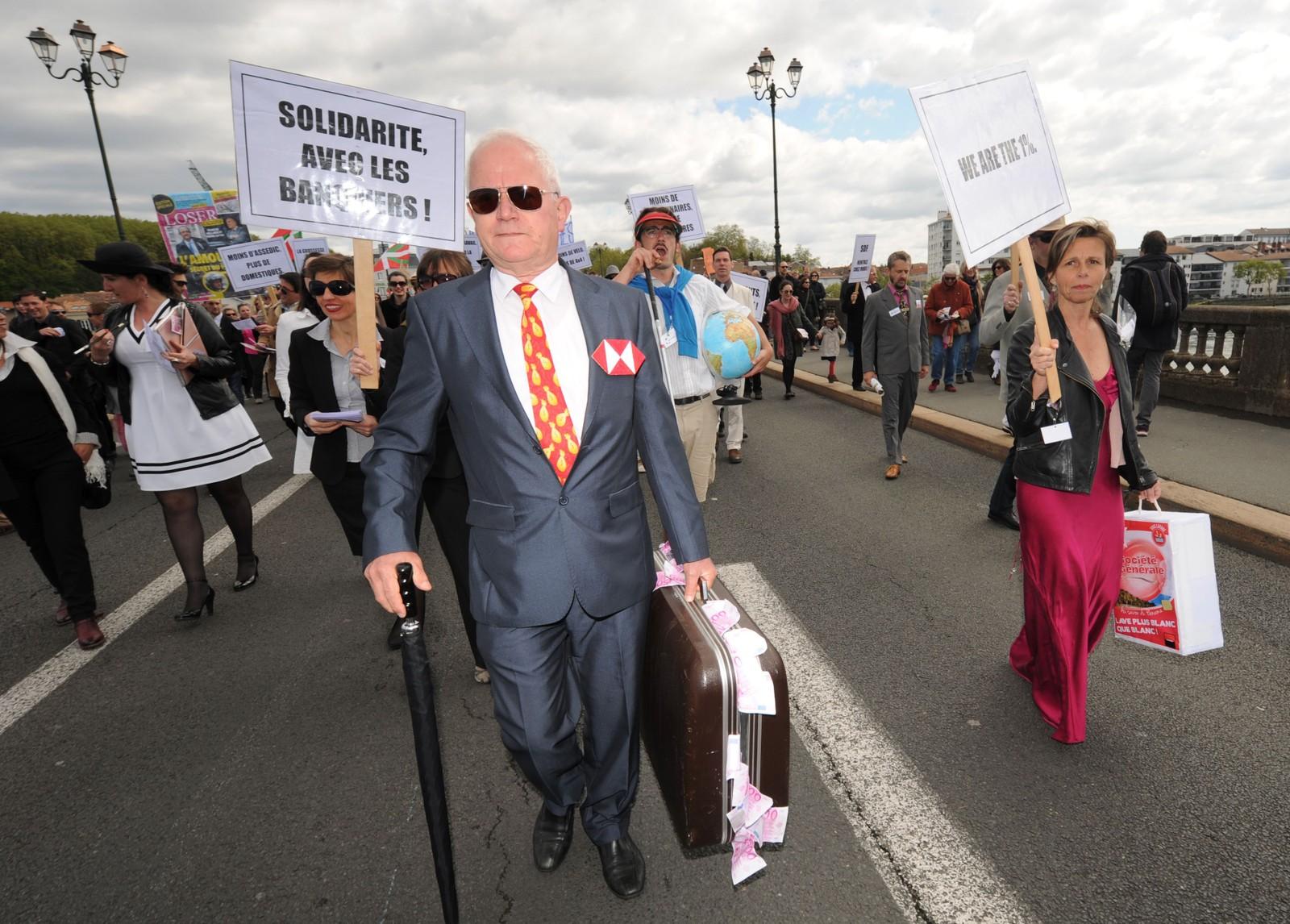En mann bærer en koffert full av falske pengesedler under en 1. mai-markering i Bayonne i Frankrike. Bevegelsen «Bizi!» gikk i tog med skilt som: «solidaritet med bankmennene».