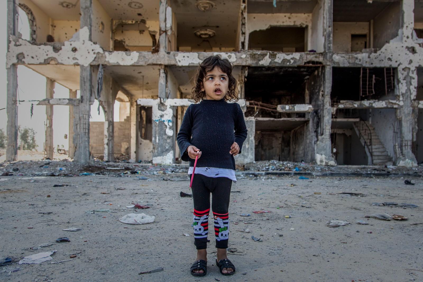 En liten jente står utenfor en av de mange bygningene som ble ødelagt under krigen mellom Hamas og Israel.