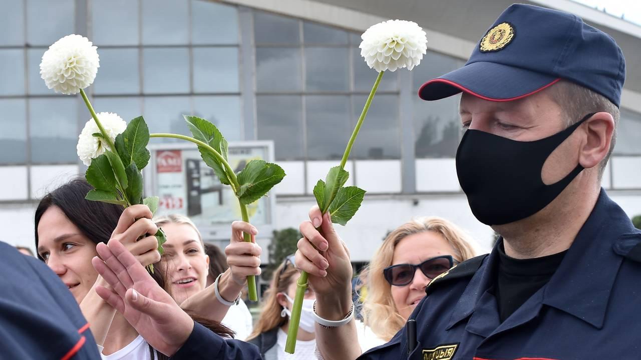 Hviterussiske demonstranter vifter med blomstene foran politiet, som ber dem fjerne seg i Minsk, Hviterussland.