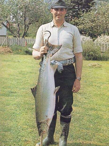 """Noverande Kong Harald V har vore ein flittig gjest i Lærdal, både på laksefiske og hjortejakt. Her er dåverande Kronprins Harald med ein laks på 13,5 kilo som han fekk i Stødnaelvi i 1973. Foto frå boka """"Sportsfiske i Lærdal"""" av John Bruvoll."""