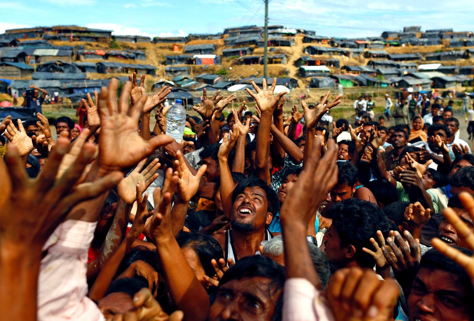Rohingya-flyktninger strekker hendene i været fordi det blir kastet hjelpemidler ut til dem i Cox's Bazar, Bangladesh.