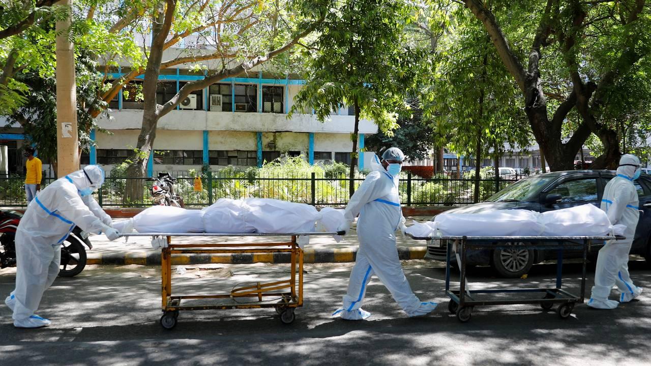 Helsearbeidere med beskyttelsesutstyr frakter døde etter koronasykdom utenfor Guru Teg Bahadur-sykehuset i New Dehli, India.