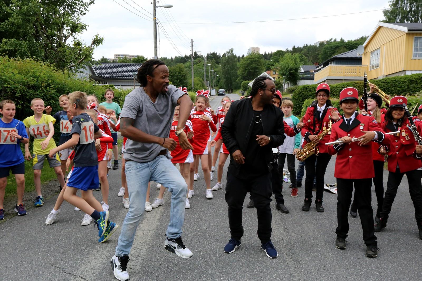 OPPTOG: I videoen danser Tshawe og Yosef fra Madcon i spissen for en prosesjon av korpsmusikanter, løpere, skatere og cheerleadere.