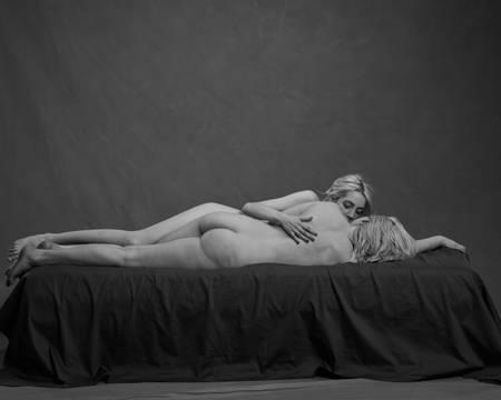 To blonde kvinner ligger nakne, side om side på en svart madrass. Hun ene ligger med rumpa mot kamera og holder rundt den andre.