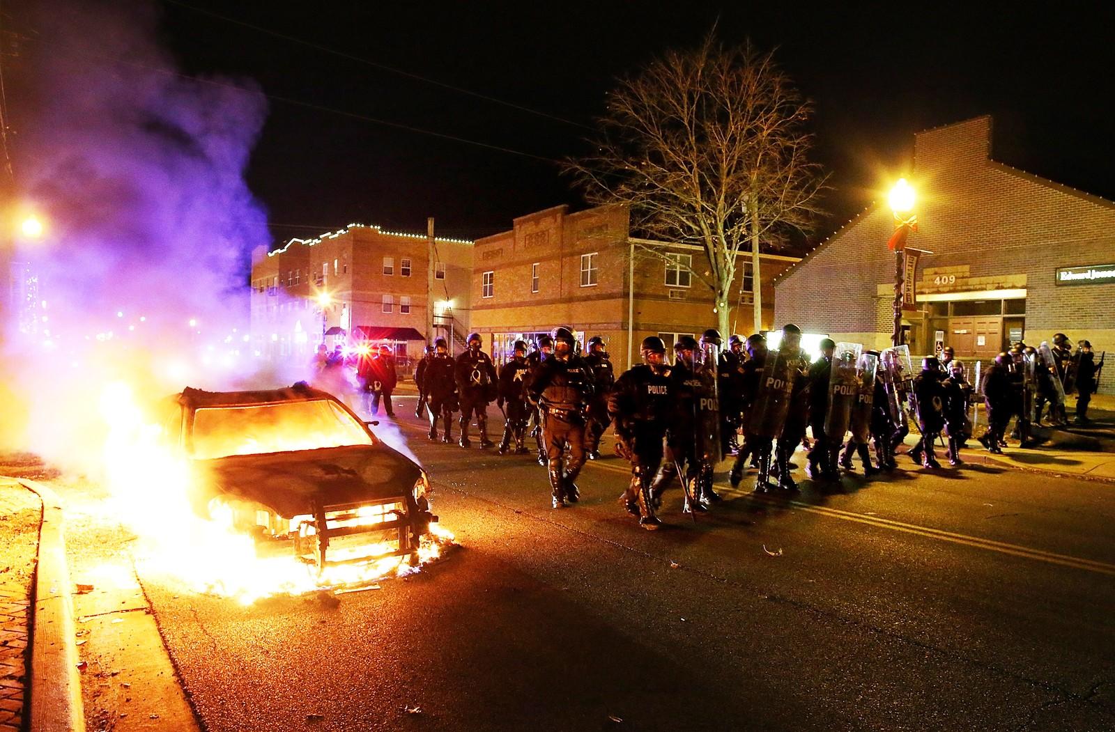 Opprørspoliti marsjerer forbi en brennende bil i Ferguson.