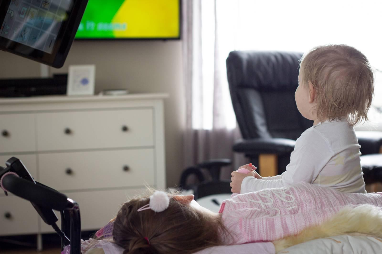 Frida Marie blir holdt i hånden av lillesøster Amalie hjemme i stua, mens de ser på TV.