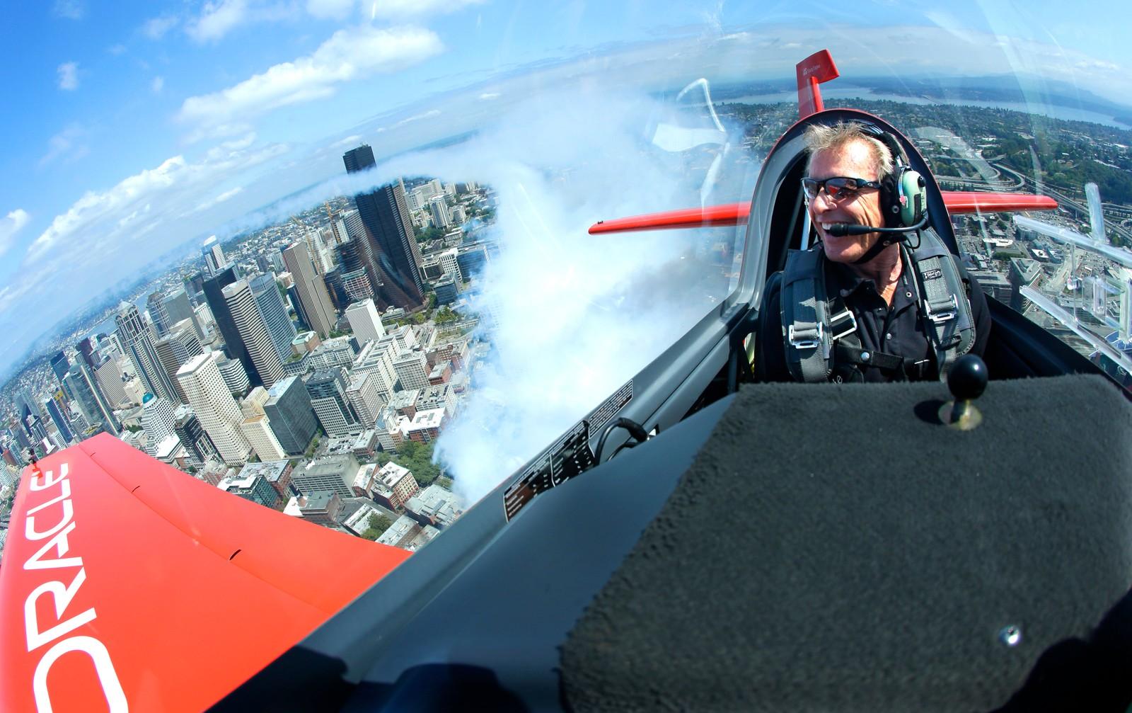 Den berømte luftakrobaten Sean D. Tucker legger igjen en stripe med røyk over Seattle den 3. august. Han forberedte seg på det årlige Seafair Airshow som startet den 5. august.