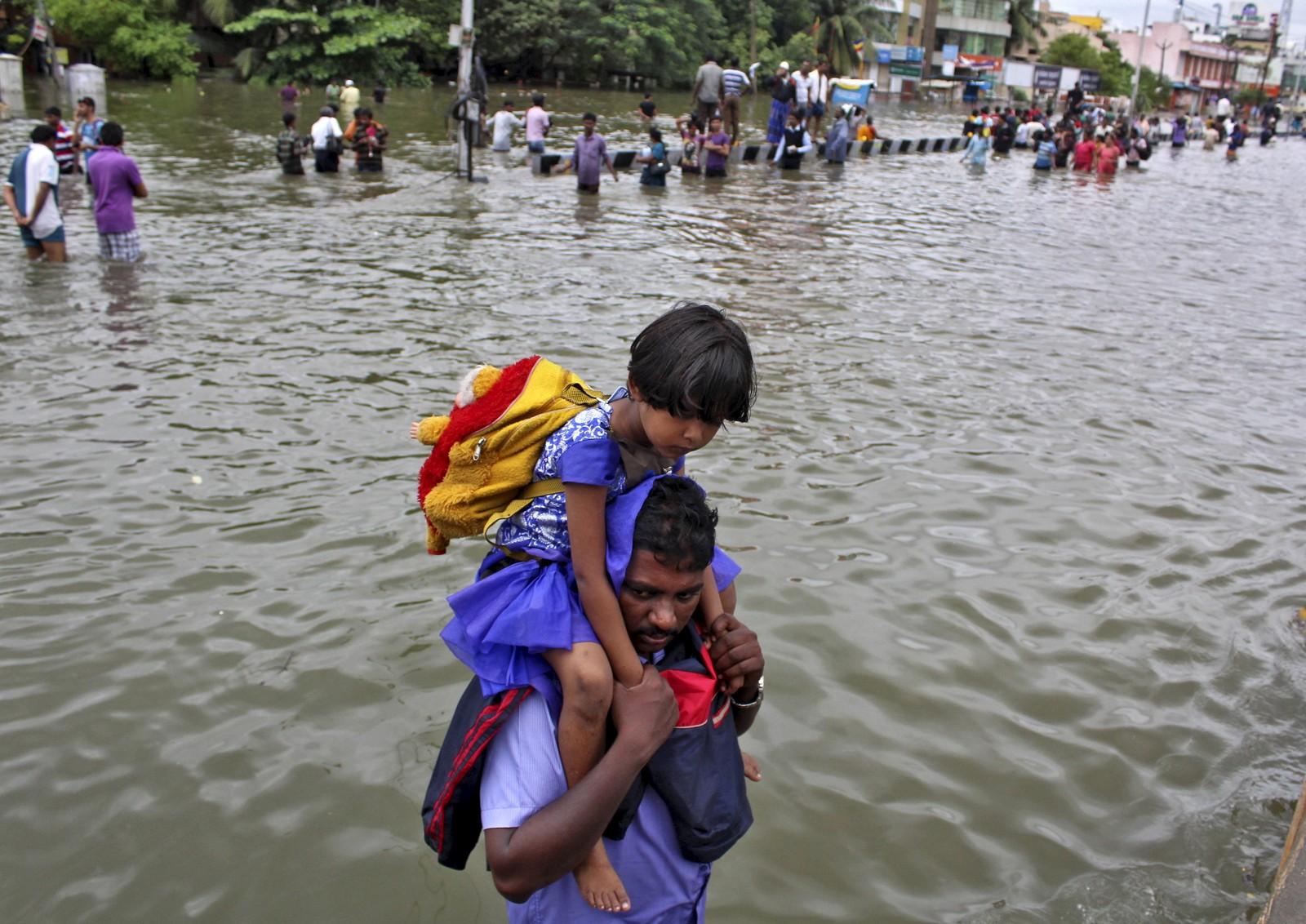 Ein mann bærer ei jente på ryggen. Dei bur begge i byen Chennai som er hardt råka av regnet.