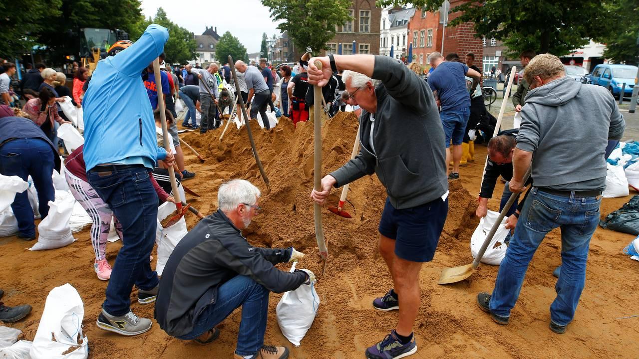 Innbyggere i Erftstad hjelper til med å fylle sand i bager som skal brukes til å hindre at vannmassene.