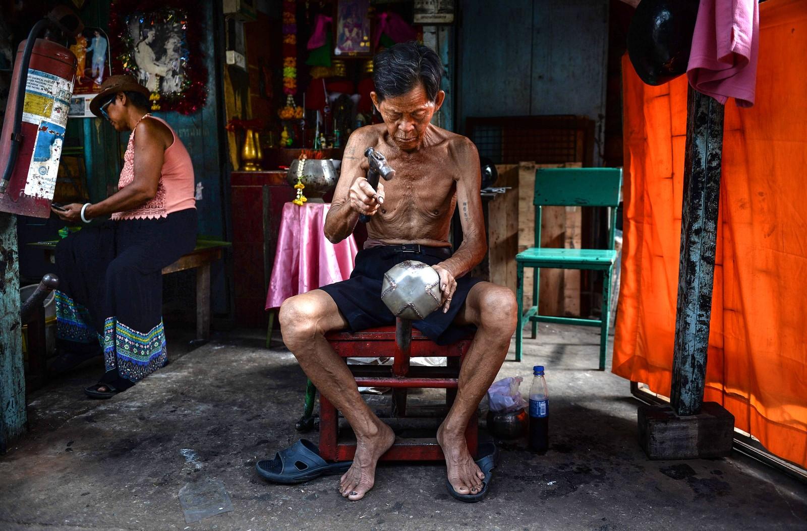 """Et eldre ektepar lager tradisjonelle buddhistiske tiggeboller før """"Khao Pansa"""", en buddhistisk fastetid som begynner den 20. juli. Dette bildet er fra Bangkok i Thailand den 14. juli. Å by på mat er et av de eldste og vanligste ritualene i buddhismen. Munkene bærer med seg bollene, og folk putter mat eller blomster i dem. Dette er ikke sett på som veldedighet. Det er vanlige menneskers plikt å støtte munkene fysisk, mens det er munkenes ansvar å passe på det spirituelle."""