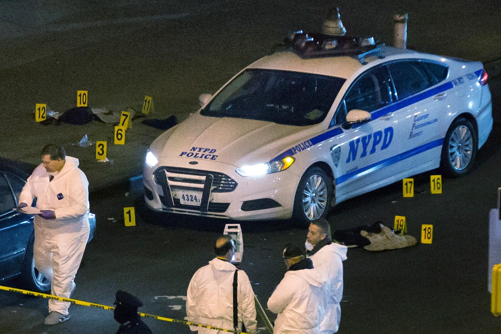 Skuddsikre vester ligger på bakken der to politimenn ble skutt og drept i New York. Etterforskere undersøker åstedet.