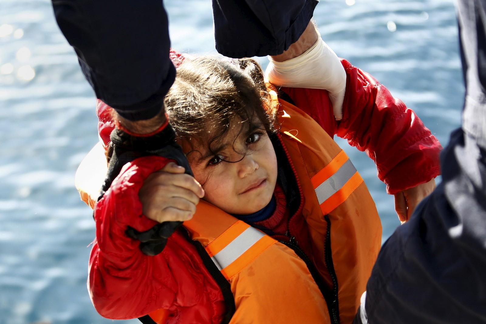 Den greske kystvakten løfter en liten flyktningjente opp fra en gummibåt, under en redningsaksjon på åpent hav midt mellom Tyrkia og den greske øya Lesbos.