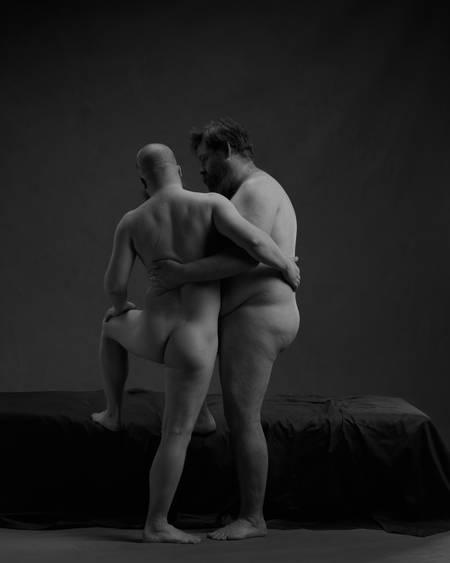 To nakne menn står med ryggen mot kamera. De holder rundt hverandre mens de ser på hverandre.