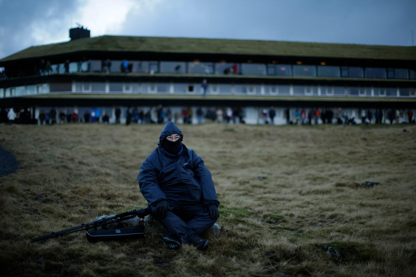En turist venter på formørkelsen på Torshavn, Færøyene.