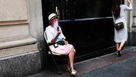 En eldre kvinne prøver å kjøle seg ned med en vifte i New York på en dag med over 35 varmegrader tidligere i august.