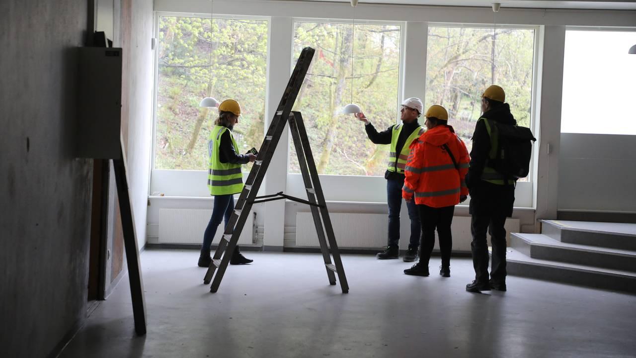 Fire mennesker står i et stort, tomt rom. En trapp skimtes til høyre. Alle har på refleksvest. De ser på tre hvite lamper som henger fra taket. De er av dansk design. En gardintrapp står midt på gulvet.