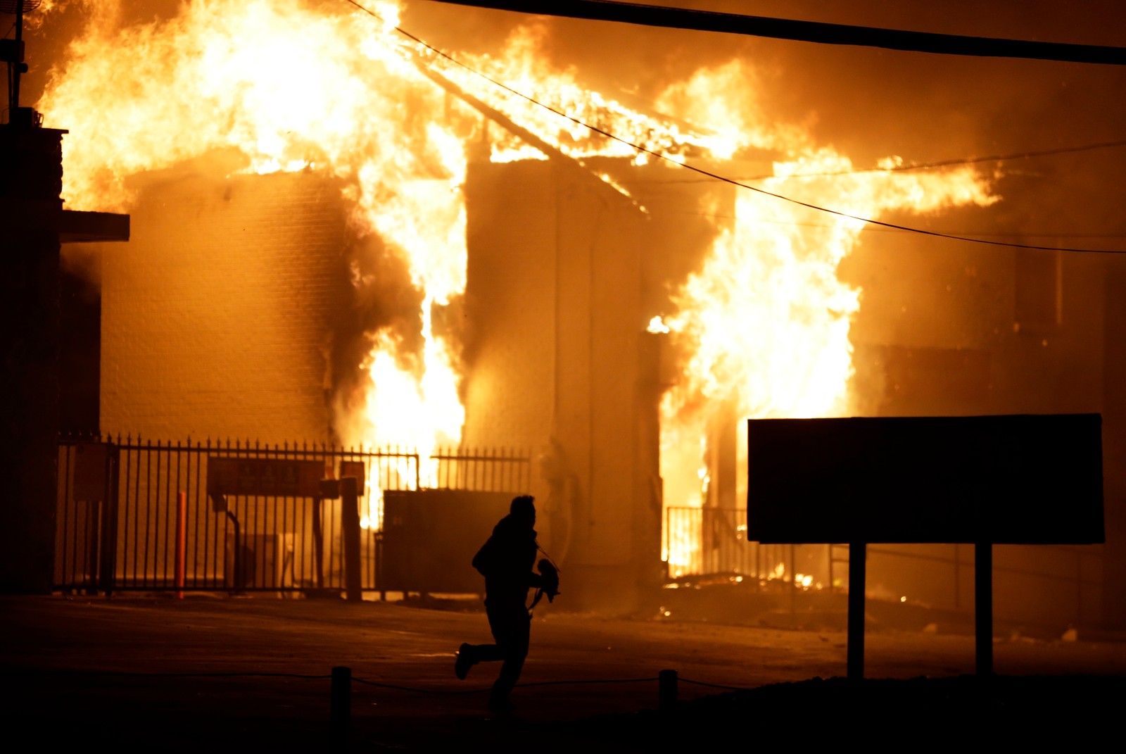 En mann løper vekk fra en brennende lagerbygning i Ferguson.