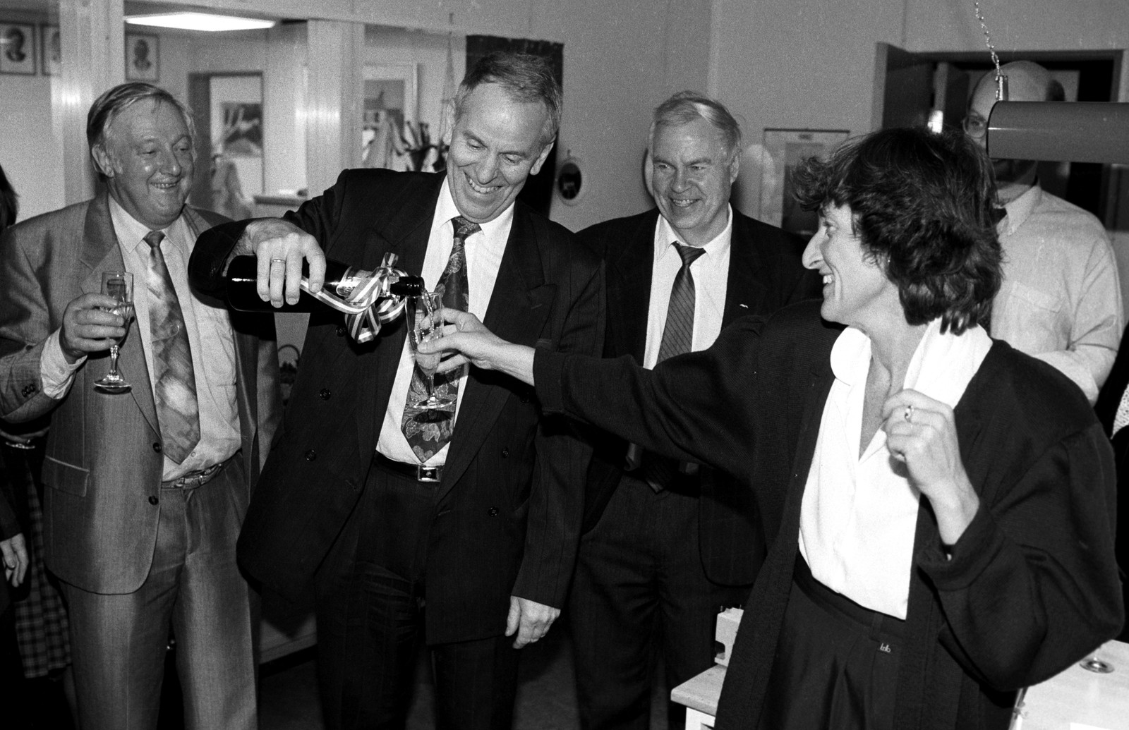 Dåverande samferdslesminister Kjell Opseth smiler breitt og skjenkar champagne til Sissel Rønbeck og kolleger etter at Gardermoen-vedtaket var eit faktum.