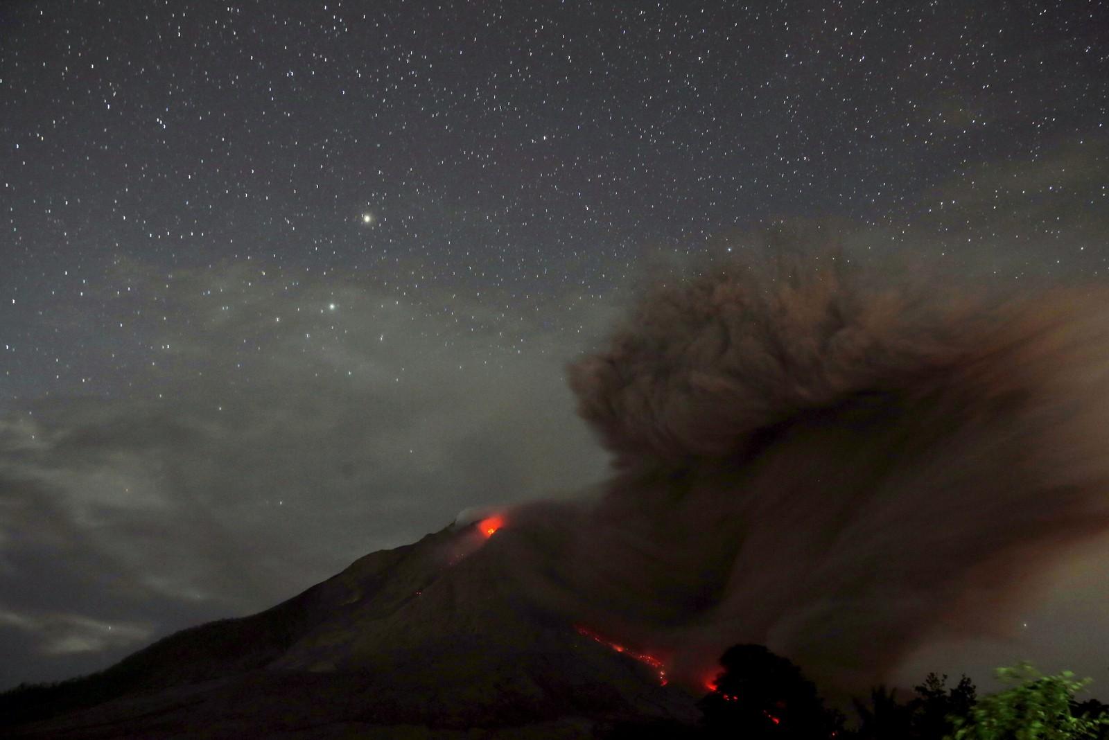 Bildet tatt 25. juli viser varm lava renner fra vulkanen Mount Sinabung i Indonesia om natta. Bildet er tatt fra byen Tiga Serankai i provinsen Nord-Sumatra.