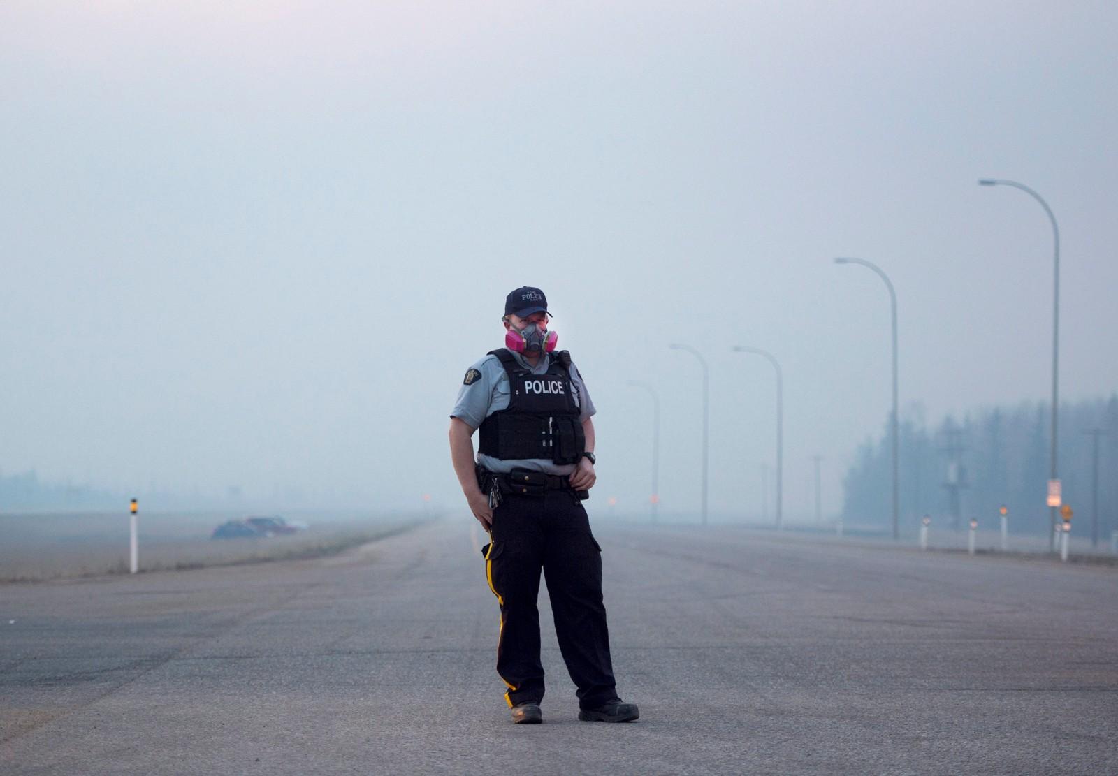 En politimann har på seg gassmaske mot røyken fra den voldsomme skogbrannen i Alberta i Canada. Skogbrannen startet rundt 1. mai og ifølge Chad Morrison, leder for avdelingen for forebygging av skogbrann i Alberta, er det ikke klart hva som er årsaken til skogbrannen. De tror imidlertid at et lynnedslag kan ha startet brannen, som oppsto i et øde område.
