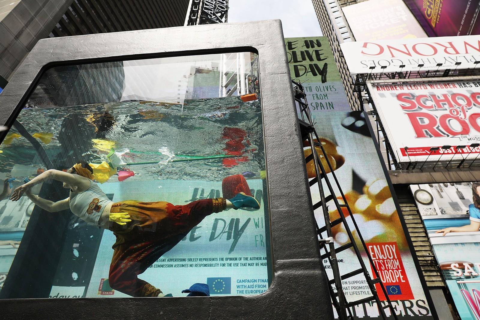 Performance-kunstneren Annie Saunders stiller for tida ut seg selv i en tank med vann på Times Square i New York. Utstillinga Holoscenes er en del av World Science-festivalen, og ønsker å sette fokus på - vann.