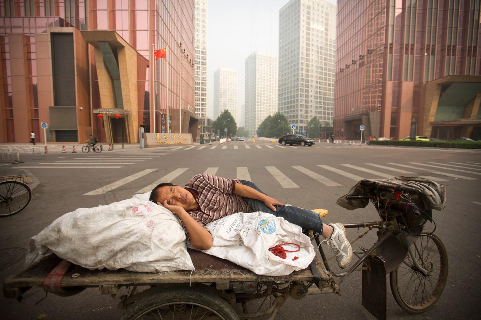 En mann tar seg en blund midt i gata på en veldig forurenset dag i Beijing. Måling av luftkvaliteten tirsdag denne uken viste nivåer som blir regnet som direkte farlige i internasjonal målestokk.