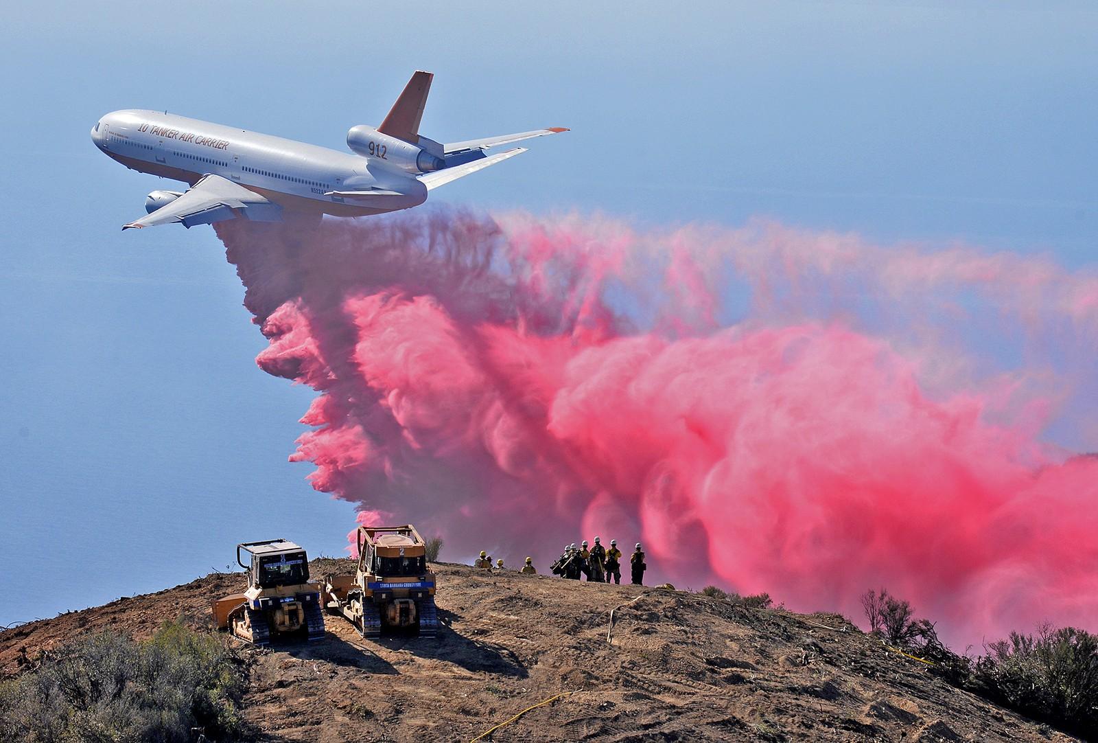 Brannmenn tar seg en pause og ser på mens et DC-10-fly tar opp kampen mot flammene i Santa Barna i California i oktober.