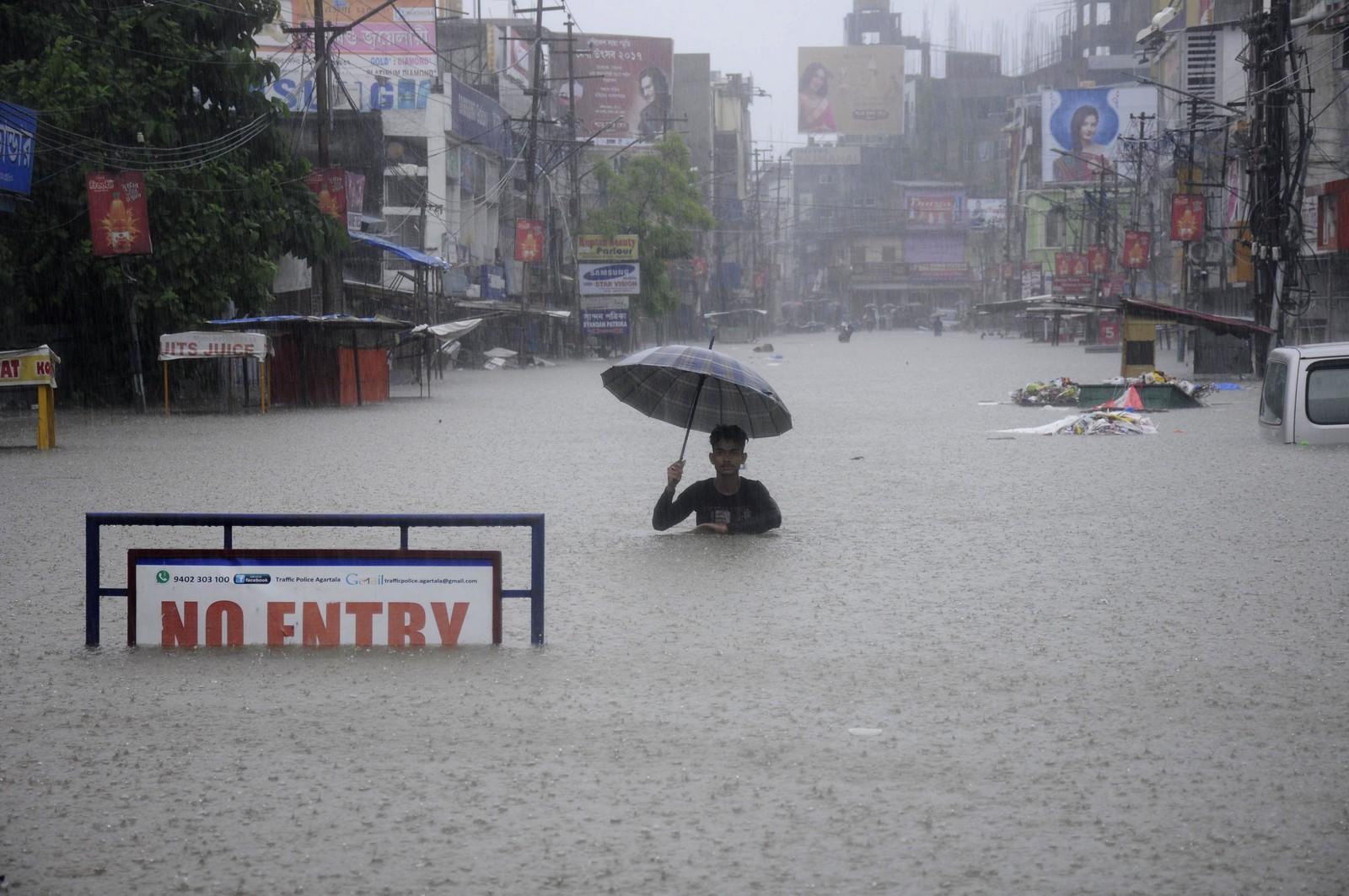 En mann med paraply i en oversvømt gate i Agartala, hovedstaden i den nordøstlige delstaten Tripura i India.