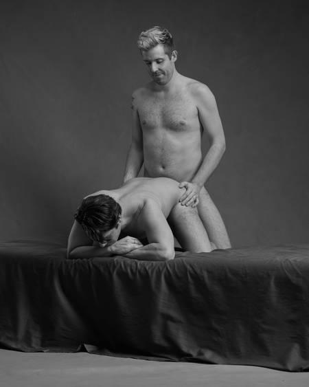 En naken mann ligger på alle fire i senga. En naken mann står bak ham inntil rumpa og holder ham på hoftene