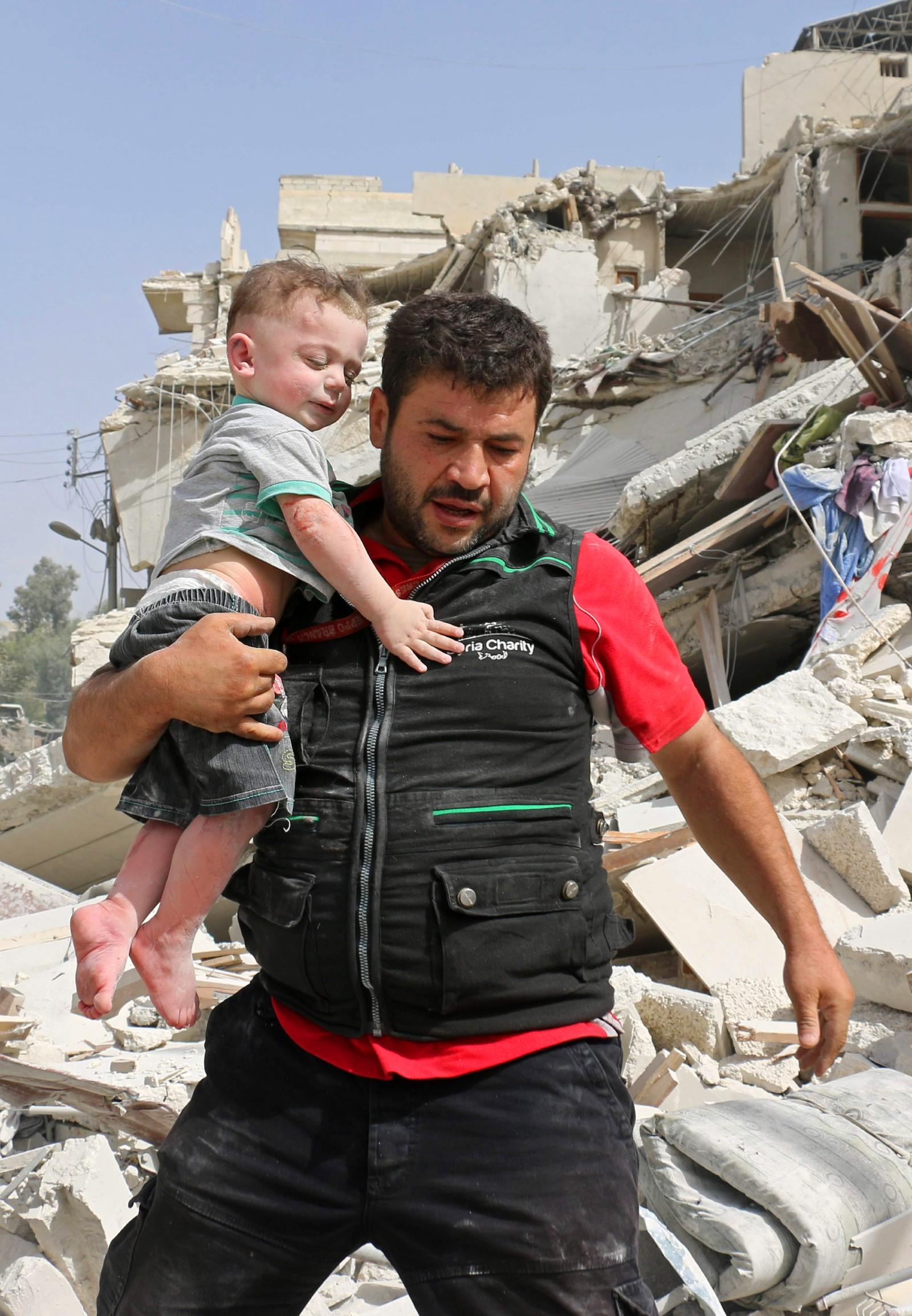 Det virker som det gikk bra denne gangen. En syrisk mann har reddet et lite barn ut fra ruinene av en bombet bygning i Aleppo den 21. september.